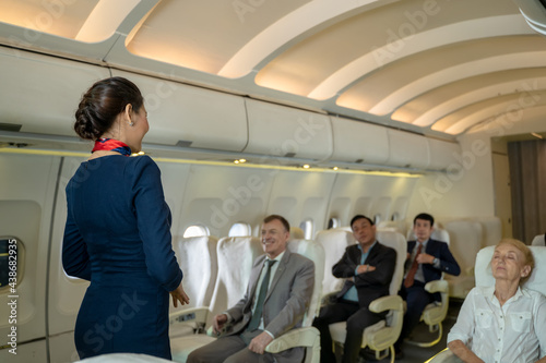 Photo Cabin crew or air hostess demonstrate safety procedures to passengers prior to flight take off in cabin airplane