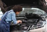 young african american mechanic working with motor of car with open hood in garage