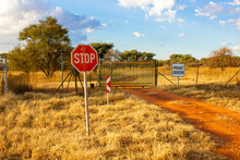 """A Green Gate With A Stop Sign And A Private Property Sign. Private Property Is Written In Afrikaans """"Privaat Eiendom"""""""