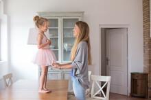 A Mother Dressing Her Daughter Of Ballerina