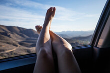 Woman Legs In A Car Window With Mountains In The Background