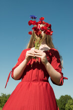 Girl In Red Dress With Bouquet Of Red Poppies Hiding Her Face In Summer