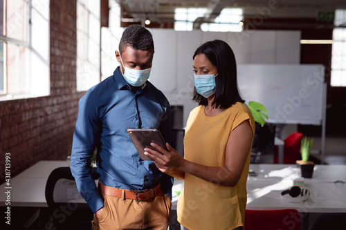 Diverse male and female colleague wearing face masks standing in office looking at tablet together