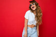 Leinwandbild Motiv Shot of beautiful amazing happy young dark blonde curly woman isolated over red background wall wearing casual white t-shirt and stylish sunglasses looking to the side