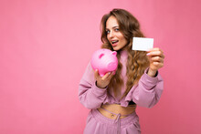 Portrait Photo Of Happy Positive Smiling Young Beautiful Attractive Woman With Wavy Long Blonde Hair With Sincere Emotions Wearing Sports Pink Hoodie Isolated Over Pink Wall With Empty Space, Holds