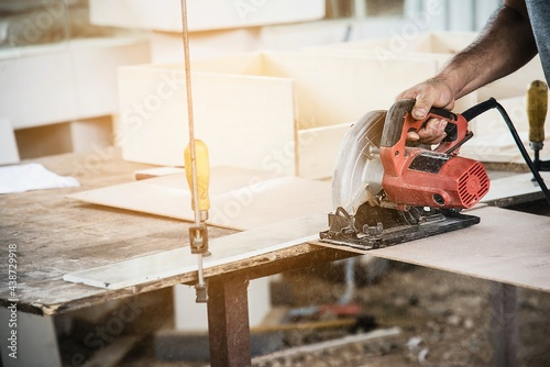 Fotografie, Obraz Carpenter working with wood furniture product preparation while cutting wood boa