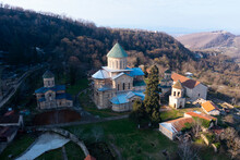 View From Drone Of Restored Ancient Gelati Monastery Of Virgin On Wooded Hillside On Sunny Spring Day. Religious And Cultural Landmarks Of Georgia .