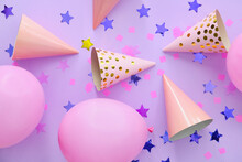 Party Hats With Air Balloons And Confetti On Color Background