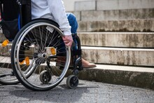 Man In Wheelchair Looking At Stairs