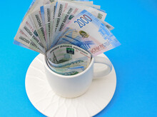 Russian Rubles In A White Cup On A Bright Colored Background. Family Budget Concept, Saving Money.