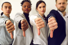 Group Of Disappointed Young Multiethnic People Give Thumbs Down, Hands In Closeup. Diverse Business Team Shows Dislike Of Bad Work Results. Multiracial Corporate HR Managers Say No And Refuse A Person