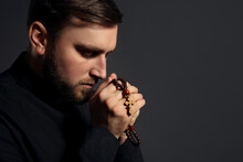Priest With Rosary Beads Praying On Dark Background. Space For Text