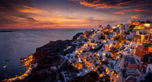 Panoramic View To The Illuminated Village Oia At The Edge Of The Caldera At Santorini Island, Greece, With The Harbour Ammoudi Below Just After Summer Sunset Time