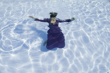 Woman In Purple Dress Floating Underwater In Swimming Pool