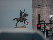 Statue Of Man Iding Horse Holding Out Sword And Red Light In Traffic