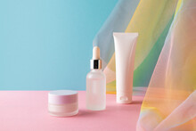 Serum, Facial Cleanser And Moisturizer Cream On Blue Pink Background With Colorful Rainbow Organza Fishnets Fabric Drapery. Beauty Products Mockup. Healthcare Skincare Concept