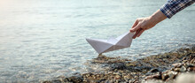 Woman's Hand Is Launching A White Paper Boat Into The Clear Water Of A Large Lake With A Stony Bottom