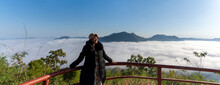 Asian Woman Standing At Terrace Viewpoint On Mountain Peak Looking At Sea Mist View At Phu Thok,  Travel Attraction In Chiang Khan District, Loei, Thailand