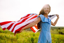 Happy Woman Posing With USA National Flag Standing Outdoors In Blooming Meadow. 4th Of July. Independence Day. Patriotic Holiday.
