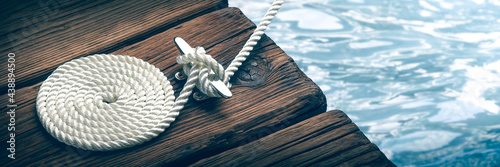 Fotografiet Coiled Boat Rope Secured To Cleat On Wooden Dock