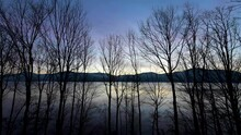 Scenic Sunrise Over Lakeside Mountain Through Barren Trees In The Winter Time Lapse