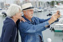 Elderly Couple Taking Selfie Harbourside
