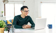 Smiling handsome asian businessman working remotely from home. He is webinar video conference..