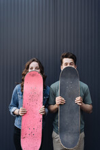Caucasian Skateboarder Couple Standing Together Prepare Themselves To Surf Skate On Gray Wall. Handsome Man And Beautiful Woman Enjoy Skateboard Exercising.Trendy Outdoor Recreation Extreme Sport