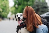 Happy woman kissing her dalmatian dog during a urban city walk. Friendship, love and care concept