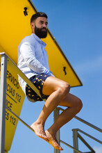 Concepto De Moda De Verano. Chico Joven Con Barba Sentado En Torre De Socorrismo Mirando Hacia El Mar.