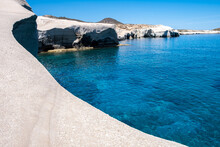 Sarakiniko Beach At Milos Island, Cyclades Greece. White Rock Formations, Cliffs And Caves Over Blue Sea