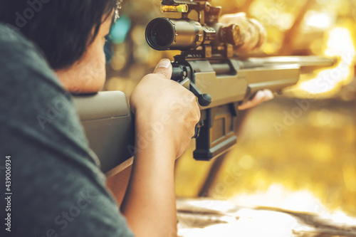 Fotografia Camouflage sniper shooting rifle by looking through a scope hunting