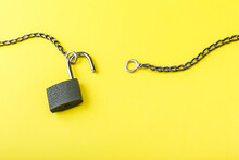 Unlocked Padlock With Chain On Yellow Background With Copy Space