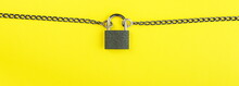 Locked Padlock With Chain On Yellow Background With Copy Space