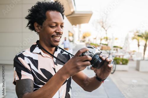Afro tourist man taking photographs with camera outdoors. Fototapeta