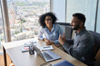 Leinwandbild Motiv Friendly happy multiethnic coworkers male indian and black female sitting at desk with laptop working together discussing successful project. Corporate business collaboration concept. Top view.