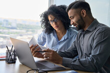 Multiethnic Male Indian Mentor And Female African American Intern Sitting At Desk With Laptop Doing Paperwork Together Discussing Project Financial Report. Corporate Business Collaboration Concept.