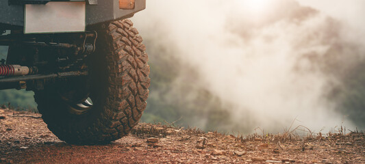 Part of an off-road vehicle on a dirt road with warm light. Adventure concept.Tire off-road on mud