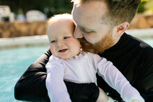 Father Embracing Baby Son (12-17 Months) In Swimming Pool