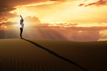 Dubai, United Arab Emirates, Woman Practicing Yoga On Sand Dune In Desert At Sunset