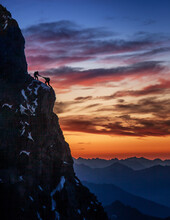 France, Haute Savoie, Chamonix, Silhouettes Of Climbers On Rocky Edge Of Mont Blanc At Sunset