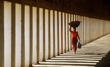 Myanmar, Bagan, Mandalay Division, Woman Walking In Portico Of Schwezigon Pagoda Carrying Wood On Her Head