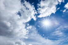 Sun Flare In Blue Sky With Clouds