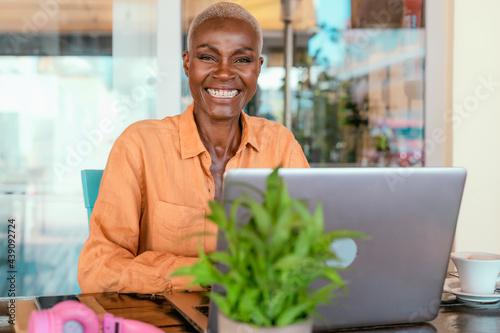 Fototapeta Happy African woman working online using laptop in bar restaurant - Digital noma