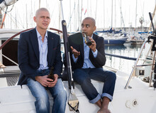 Men In Jackets And With Tacked Jeans Sit And Drink Beer On A Yacht In Seaport