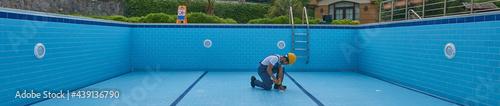 Fotografia Repairman is repairing pool with equipment