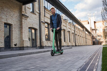 Man Going Somewhere On An Ecological Electric Scooter Through The Urban Street