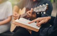 A Young Boy Reads The Bible While His Friend Plays The Guitar. When He Worships God A Small Group Of Christians Or Concepts In A Church At A Church.