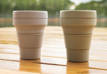 Two Reusable Eco Cups On Wooden Table In Nature. Sustainable Lifestyle And Zero Waste Concept.