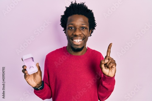 Fototapeta Young african american man holding engagement ring for proposal smiling with an